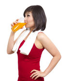 Pretty asian girl drinking orange juice after exercise — Stock Photo