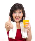 Bella asiatica ragazza alzando succo d'arancia e i pollici — Foto Stock