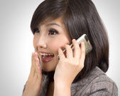 Young Asian businesswoman exited while talking on cellphone — Stock Photo
