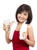 Chica bonita asiática sosteniendo un vaso de agua después del ejercicio — Foto de Stock