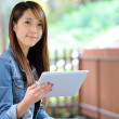 Young asian woman with tablet computer outdoor — Stockfoto
