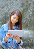 Young asian woman with tablet computer outdoor — Стоковое фото