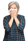 Sneezing mature asian woman — Stock Photo