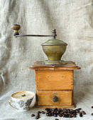 Ancient coffee grinder with grains — Stock Photo