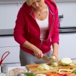 Young lady making salad in kitchen — Stockfoto
