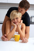 Happy couple posing in the kitchen with cups — Stock Photo