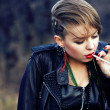 Blond hipster girl with leopard haircut smoking cigarette alone — Stock Photo #8082887