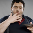 Stock Photo: Funny fat guy eating chocolate cake