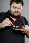 Funny fat guy eating chocolate cake — Stock Photo