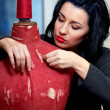 Seamstress repairs red old mannequin with her hands in her works — Stock Photo