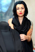 Mannequin wrapped with black cloth with girl with tattoo behind — Stock Photo