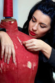 Näherin repariert rot alte schaufensterpuppe mit ihren händen in ihren werken — Stockfoto