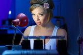 Seductive blond sewing in her workshop — Stockfoto