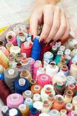Female hands choosing thread — Stock Photo