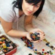 Young seamstress choosing buttons — Stock Photo #8584802
