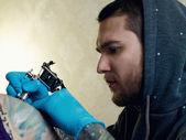 Bearded Caucasian tattooist creates a tattoo on a woman's should — Stock Photo