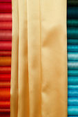 Colored bobbins and golden silk — Stock Photo