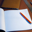 New square lined exercise book with orange pen — Stock Photo