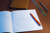 New lined exercise book with orange pen — Stock Photo