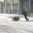 Man shoveling snow during snow storm - Stock Photo