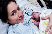 Happy mother holding newborn baby after birth — Stock Photo