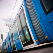 Blue tram in a city background — Stock Photo
