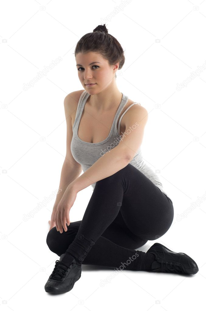 Beautiful young caucasian brunette woman wearing sportswear sitting on the white floor. Isolated against white background — Stock Photo #9399456