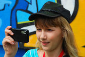 Young girl taking photo with mobile phone — Stock Photo