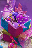 Colorful gift boxes with christmas baubles — Stock Photo