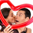Young couple kissing through balloon heart surprise isolated — Stok fotoğraf