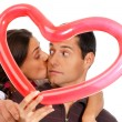 Young couple kissing through balloon heart surprise isolated — 图库照片