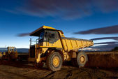 Huge auto-dump yellow mining truck night shot and excavator — Stock Photo