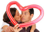 Young couple kissing through balloon heart surprise isolated — Stock Photo