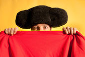 Bullfighter afraid with big montera hidden behind cape humor spanish colors — Stock Photo