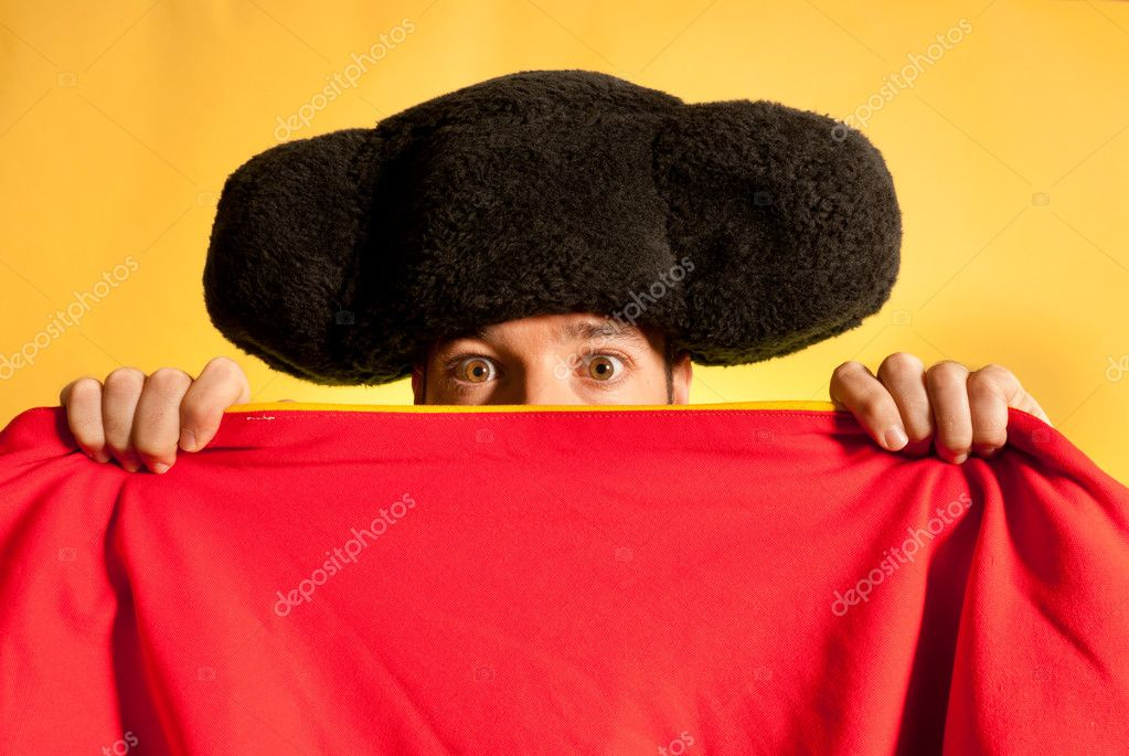 Bullfighter afraid with big montera hidden behind cape humor spanish colors  Stock Photo #8810135