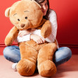 Young woman embracing teddy bear sitting on floor — Stock Photo