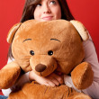 Young woman embracing teddy bear looking up sitting close-up — Stock Photo