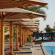Plank beds under umbrellas at pool in hotel. Egypt — Stock Photo
