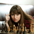 The girl with chess on a sofa — Stock Photo