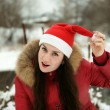 Stock Photo: The girl in wood in a hat of Santa Claus