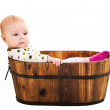 Cute infant girl sitting in wooden bucket — Stock Photo