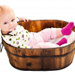Stock Photo: Cute infant girl sitting in wooden bucket