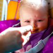 Unhappy infant girl learning to eat solid food — Stock Photo
