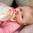 Mother feeding infant girl with a milk bottle — Stock Photo