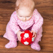 Cute infant baby girl sitting on the floor — Stock Photo #9447514