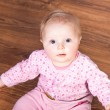 Cute infant baby girl sitting on the floor — Stock Photo #9447532