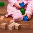 Infant girl playing in room on wooden floor — Stock Photo #9447549