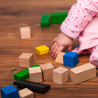Infant girl playing in room on wooden floor — Stock Photo