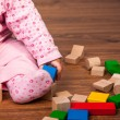 Infant girl playing in room on wooden floor — Stock Photo #9447557