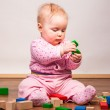 Infant girl playing in room on wooden floor — Stock Photo #9447559
